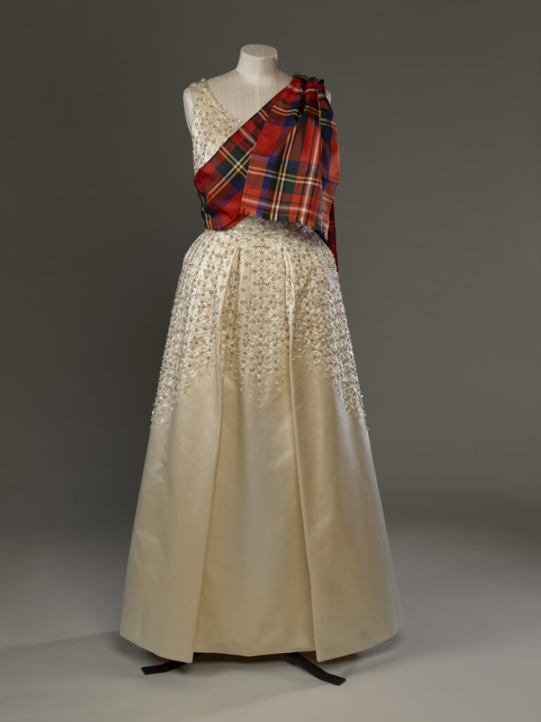 For the dances, which were originally instituted by Queen Victoria, gentlemen of the Royal Family wear Highland Dress while royal ladies wear long evening dresses with Royal Stewart tartan sashes. Sir Norman Hartnell (1901-79) / Evening Dress 1960-70 Royal Collection Trust/All Rights Reserved
